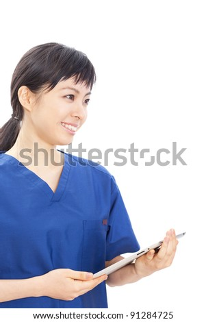 young woman doctor in scrubs using tablet computer isolated on white background - stock photo