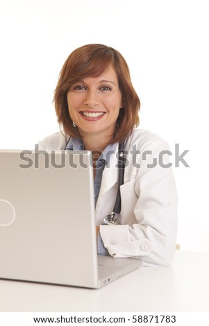 Young woman doctor in white coat at computer - stock photo