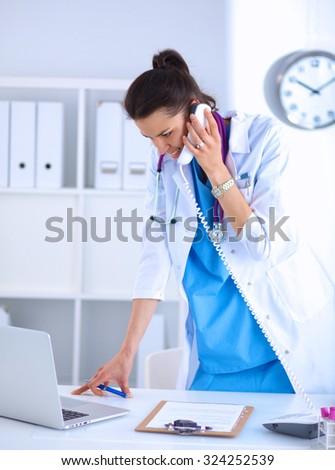 Young woman doctor in white coat at computer using phone - stock photo