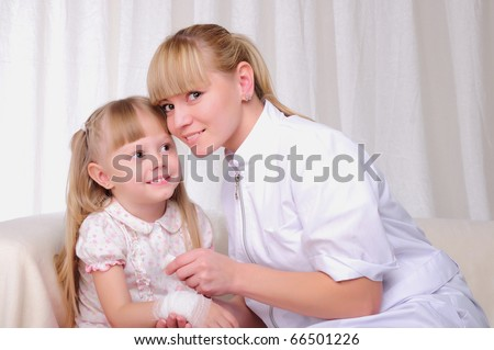 Young woman doctor is dripping a drop in the spout of his little patient - stock photo