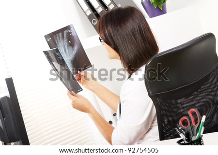 Young woman doctor is looking at xray of broken hand - stock photo