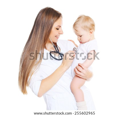 Young woman doctor listens to the heart of a child - stock photo