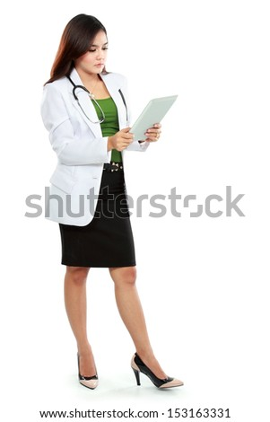 Young woman doctor using tablet computer isolated over white background