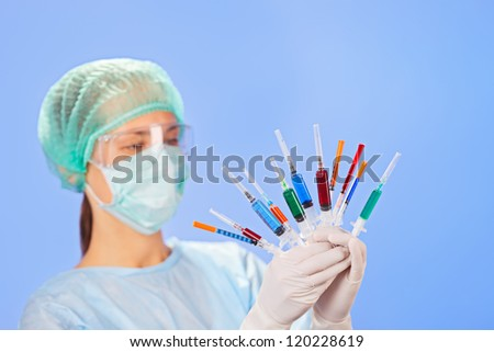 Young woman doctor with many multicolor syringes in hands on blue - stock photo