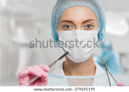 Young woman doctor with scalpel and scissors in surgery room interior - stock photo