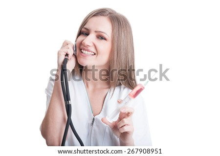 Young woman doctor with stethoscope and syringe playing on white background - stock photo