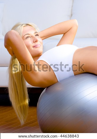 Young woman does crunches on a balance ball in the living room.  Vertical shot. - stock photo