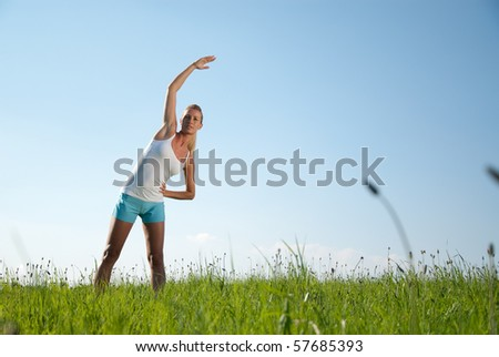 young woman does stretching exercises outdoors - stock photo