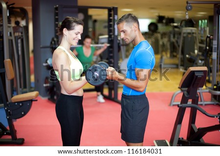 Young woman doing a bicep exercise with the help of a personal trainer at the gym - stock photo