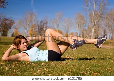 Young woman doing a bicycle ab exercise. - stock photo