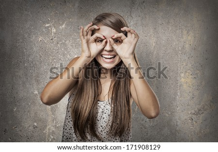 young woman doing a glasses sign against a grunge wall - stock photo