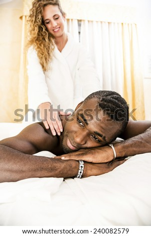 Young woman doing a massage at her boyfriend. Lovely mixed race couple. - stock photo