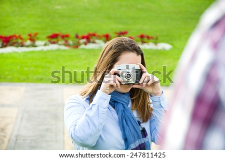 Young woman doing a photo to her boyfriend in the park - stock photo