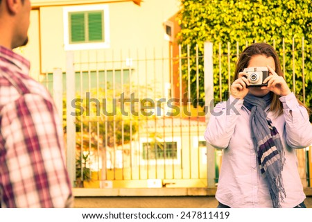 Young woman doing a photo to her boyfriend in the park vintage - stock photo