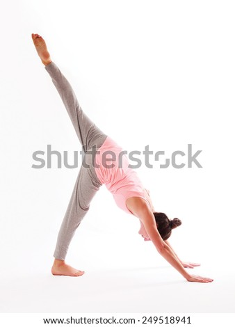 Young woman doing a yoga posture on a white background   - stock photo