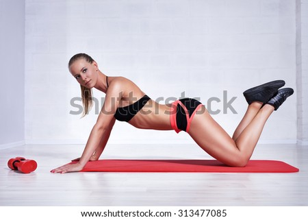 Young woman doing abdominal fitness exercises in bright white interior.