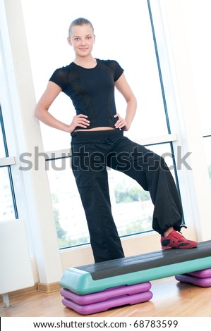 Young woman doing aerobic exercises at the sport gym - stock photo