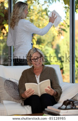 Young woman doing chores for a senior - stock photo