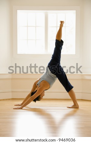 Young woman doing downward dog pose with one leg raised on wooden floor indoors by sunlit window. - stock photo