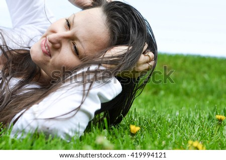 Young woman doing exercise on the grass.  Healthy lifestyle. Recreation in the park - stock photo