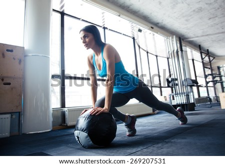 Young woman doing exercise with fit ball at gym - stock photo