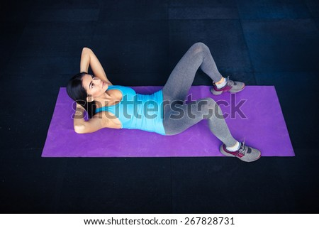 Young woman doing exercises abs on yoga mat at gym  - stock photo