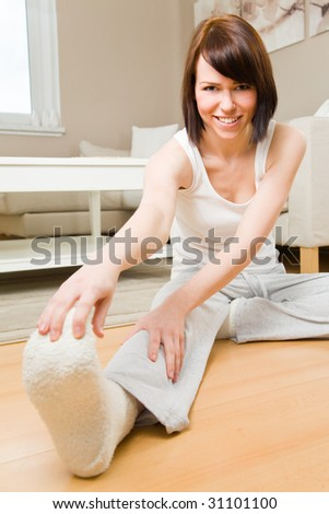 Young woman doing exercises in her living room - stock photo