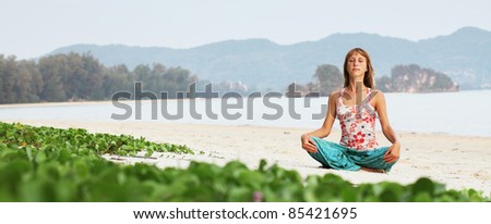 Young woman doing exercises on sand on blue sky background - stock photo