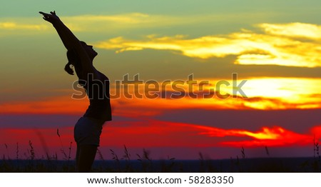 Young woman doing exercises under sunset light - stock photo