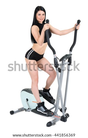 young woman doing exercises with elliptical cross trainer, isolated on white background - stock photo
