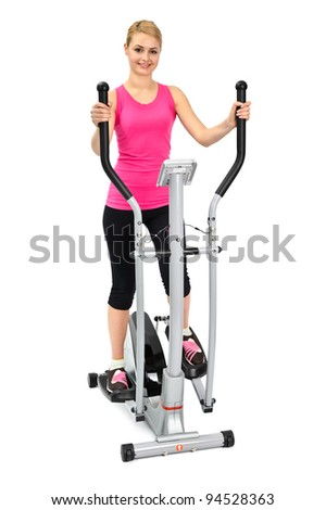 young woman doing exercises with elliptical trainer, on white background - stock photo