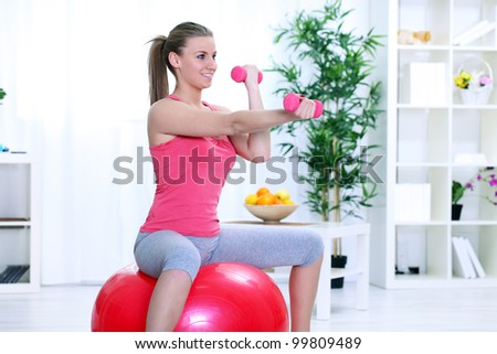 Young woman doing fitness exercise with dumbbell and sitting on fitness ball