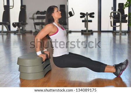Young woman doing fitness exercises on stepper at gymnasium - stock photo