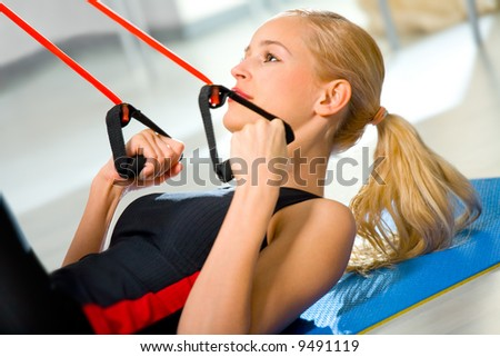 Young woman doing fitness exercises with expander at home - stock photo