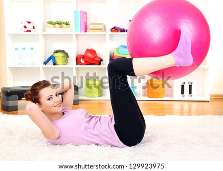 Young woman doing fitness exercises with gym ball at home - stock photo