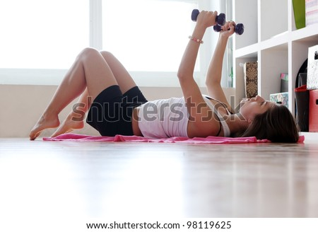 Young woman doing gymnastic exercises at home - stock photo
