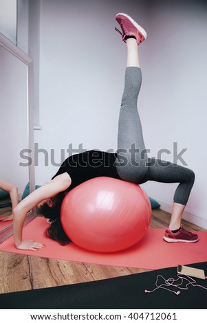 Young woman doing gymnastics with ball in the home studio
