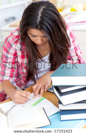 Young woman doing her homework at a table - stock photo