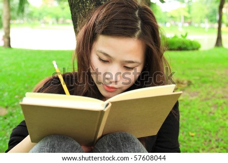 young woman doing homework in the park