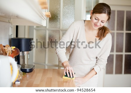 Young woman doing housework, cleaning the kitchen - stock photo