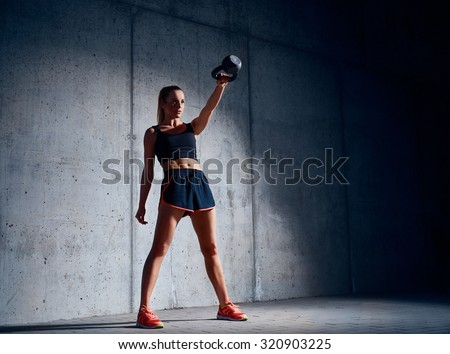 Young woman doing kettlebell swing exercise - stock photo