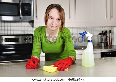 Young woman doing kitchen cleaning chores with rubber gloves - stock photo