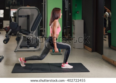 Young woman doing legs exercises on a gym mat indoor with dumbbells - stock photo