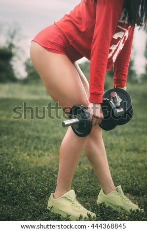 Young woman doing lunges with dumbbells in the forest