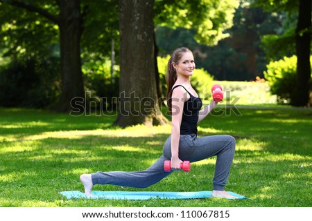 Young woman doing lunges with dumbbells in the park - stock photo