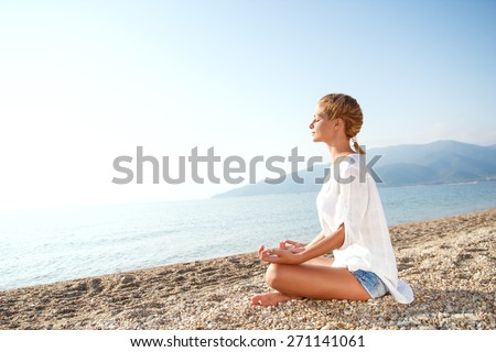Young Woman doing meditation in lotus position on the beach.