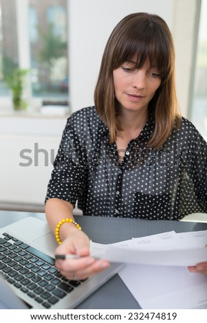 Young woman doing paperwork in the office sitting at her desk reading a report with a pen in her hand for notations - stock photo
