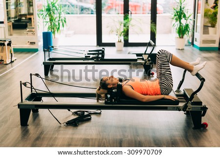 Young woman doing pilates reformer workout exercises at indoor gym. - stock photo