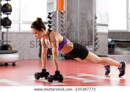 Young woman doing plank position with dumbbells - stock photo