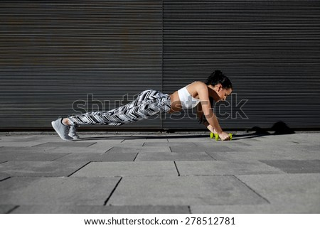 Young woman doing press ups with dumbbells while standing on black background outdoors, athletic female in workout gear doing push-ups with some weights against wall with copy space for text message - stock photo